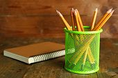 Pencils in metal holder near notebook on rustic wooden background