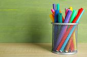 Colorful markers in metal holder on wooden table and green wooden background