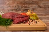 raw beef meat with vegetables on wooden plate.