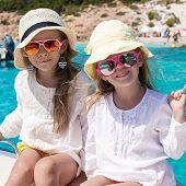 Portrait of little cute girls enjoying sailing on boat in the open sea