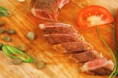 fresh roasted beef meat steak sliced on wooden board with cutlery isolated  over white background