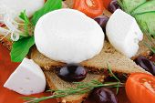 mozzarella cheese on red with bread and olives