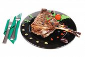 roasted ribs on black plate with cutlery