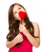Portrait of a little girl holding red heart and daydreaming, isolated over white