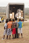 Children wating for donated Christmas gifts to be unloaded from the delivery truck.