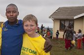 Volunteer aid worker standing beside a Zulu youth at an orphanage.