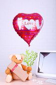 Teddy bear with present box, tree and love heart balloon on wooden  computer table, on the brick wall background