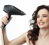 portrait of attractive  caucasian woman  with long  hair brunette isolated on white studio shot making hairstyle with hair drier