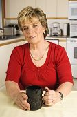 Senior Woman Taking A Coffee Break In Her Kitchen