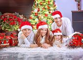 Big happy family wearing Santa hat, celebrating Xmas at home near beautiful decorated Christmas  tree, spending winter holidays together concept