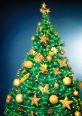 Beautiful Christmas tree over blue background, luxury golden decoration, traditional symbol of Christmastime holidays