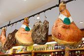 Prosciutto di parma hams in a shop, trademarks deleted