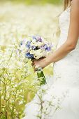 foto of sanctification  - Bride in white dress holding a bouquet of flowers and standing in a field