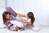 Beautiful girls twins in pajamas fight pillows at home