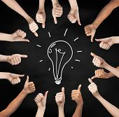 gesture, people, idea and development concept - human hands showing thumbs up in circle over black board background with drawing of lightning bulb in center