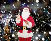christmas, holidays, gesture and people concept - man in costume of santa claus with notepad pointing finger up over snowy night city background