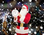 christmas, holidays and people concept - man in costume of santa claus with clock showing twelve pointing finger over snowy night city background