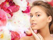 beauty, people and health concept - beautiful young woman touching her face over pink floral background