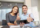 business, people, technology and teamwork concept - smiling businessman and businesswoman with tablet pc computer showing thumbs up gesture meeting in office