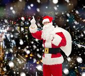 christmas, holidays, gesture and people concept - man in costume of santa claus with bag pointing finger up over snowy night city background