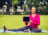 fitness, park, technology and sport concept - smiling african american woman with tablet pc computer sitting on mat outdoors