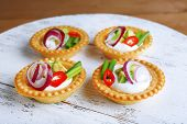 Tartlets with greens and vegetables with sauce on tray close-up