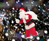 christmas, holidays and people concept - man in costume of santa claus running with bag over snowy night city background