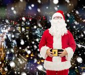 christmas, holidays and people concept - man in costume of santa claus over snowy night city background