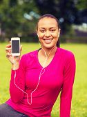 fitness, park, technology and sport concept - smiling african american woman with smartphone and earphones outdoors