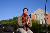 Asian student sitting holding book at campus