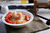 Boiled rice and shrimps, salmon and tomatoes in bowl, on wooden background
