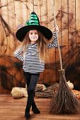 Little girl Witch in hat with broom on Halloween decorations background