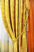 stock photo of tassels  - Detail shot with a yellow curtain decorative tassel - JPG