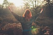 Woman Raising Arms Joyfully At Sunset In Forest