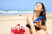 Woman Feeling The Warm Sun On Tropical Beach While Putting Sun Lotion