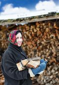 woman in ethnic costume with firewood