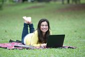Beautiful young asian female university or college student lying on stomach with books, files and an open laptop in a park.