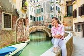 Happy Young Woman Sitting On Bridge In Venice, Italy And Looking