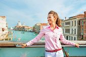pic of piccolo  - Happy young woman standing on bridge with grand canal view in venice italy - JPG