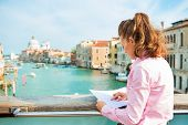 image of piccolo  - Young woman standing on bridge with grand canal view in venice italy and looking at map - JPG