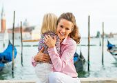 Portrait Of Happy Mother And Baby Hugging On Grand Canal Embankment In Venice, Italy