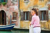 Portrait Of Happy Young Woman Standing On Street In Venice, Ital
