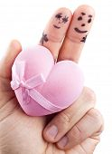 Couple painted on man's fingers and gift box in the form of heart.