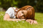 Pretty redhead napping on grass in park at sunlight