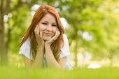 Portrait of a pretty redhead content and lying on grass
