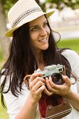Happy brunette in straw hat holding retro camera in the park