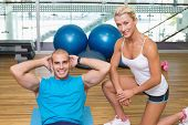 Smiling female trainer assisting young man with abdominal crunches at fitness studio