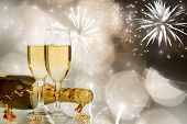 Glasses with champagne and bottle over fireworks and sparkling holiday background
