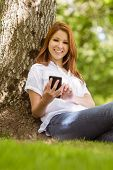 Pretty redhead smiling and holding her phone in park on a sunny day