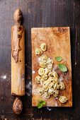 Homemade Raw Tortellini And Basil Leaves On Dark Wooden Background